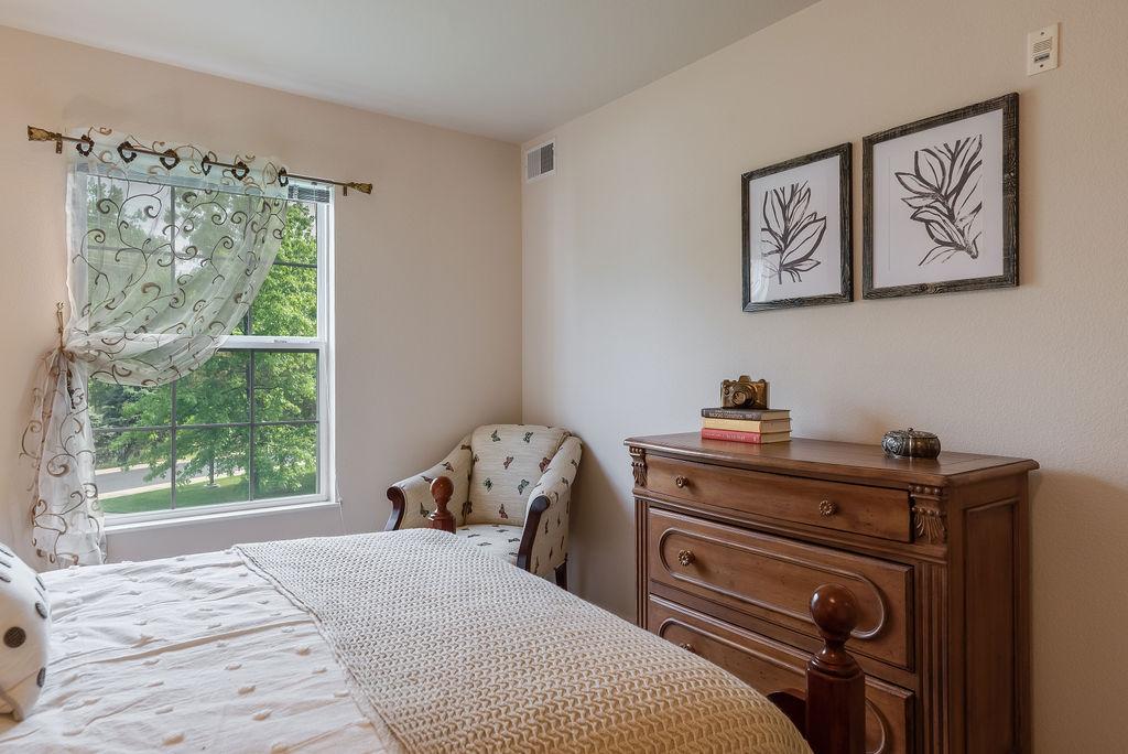 Bedroom with window and dresser in Elmhaven Manor